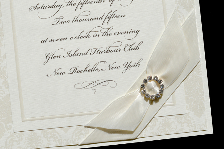 A multi-layer invitation with elegant papers and a rhinestone brooch.