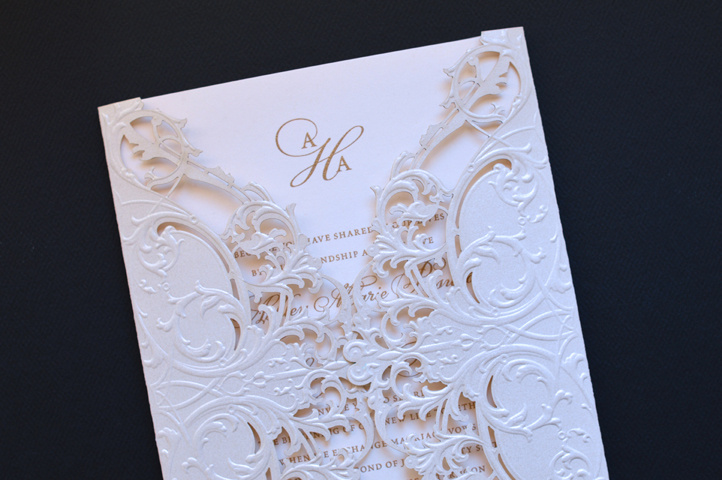 A stunning laser cut wrap in ivory shimmer paper surrounds this invitation.
