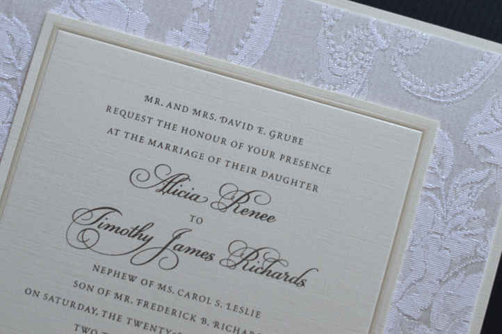 A multi-layered invitation featuring brocade fabric.