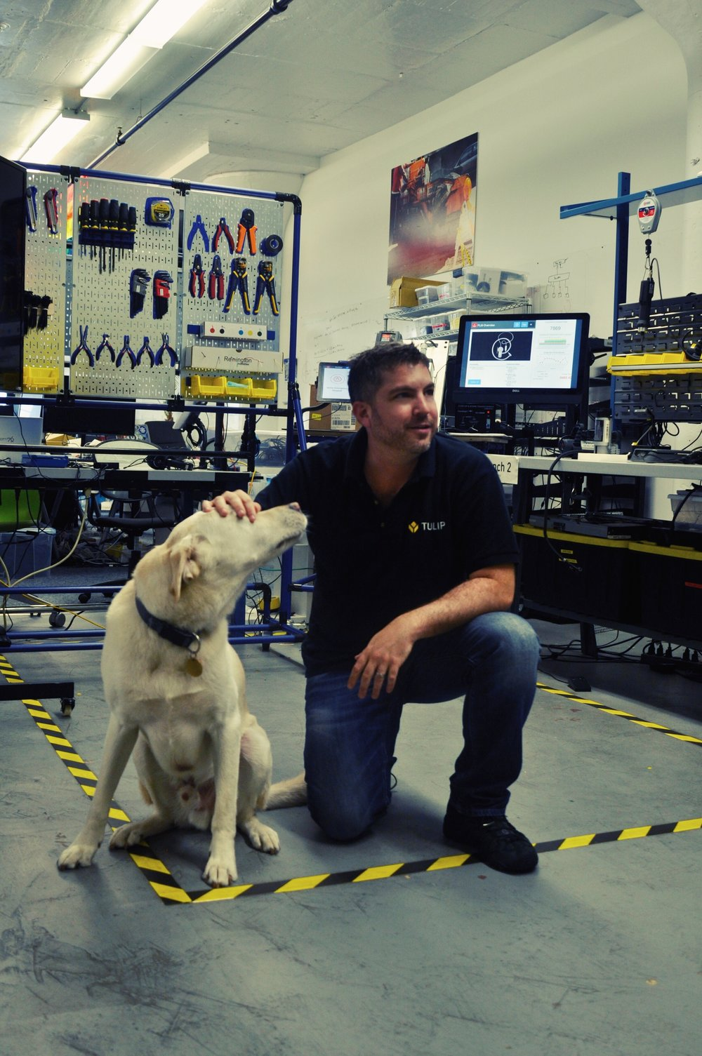Natan Linder with his dog, Charlie, inside the Tulip offices headquartered in a Somerville warehouse.  Photo by Grace Gulick.