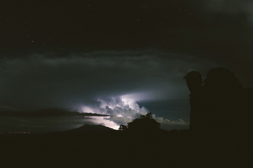 Lightning erupts behind distant clouds