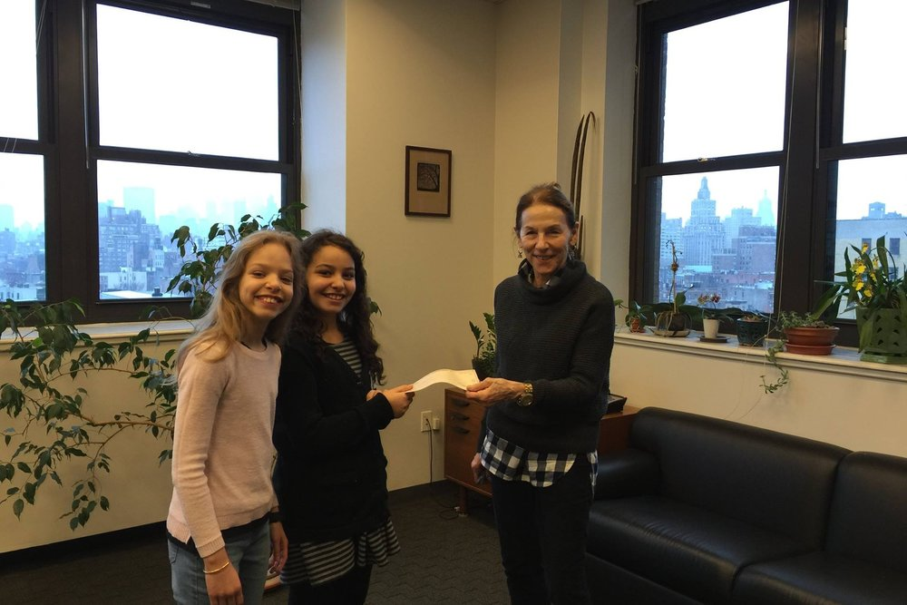 Jasmine and Angelina deliver their check to Deputy Director, Stephanie Cowles