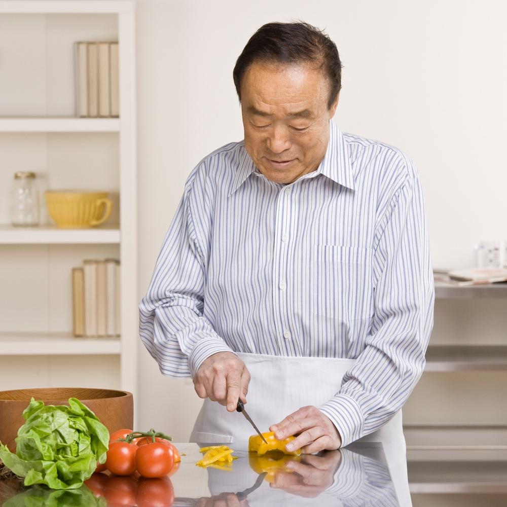Asian man cutting veggies for salad.jpg