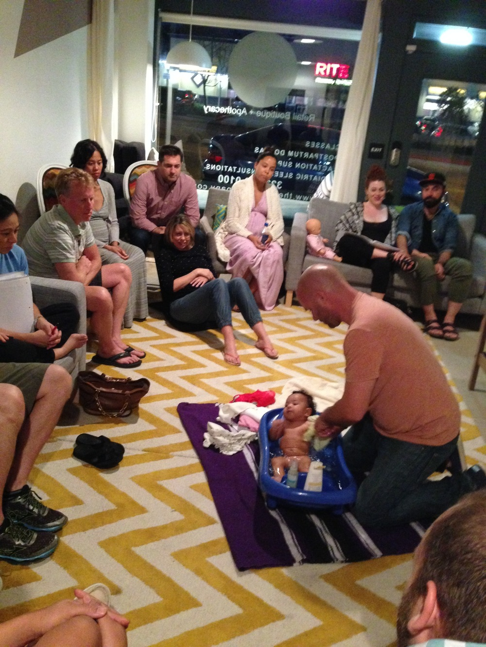 "Daddy lovingly demos baby's first bath in ""baby Care"" class"