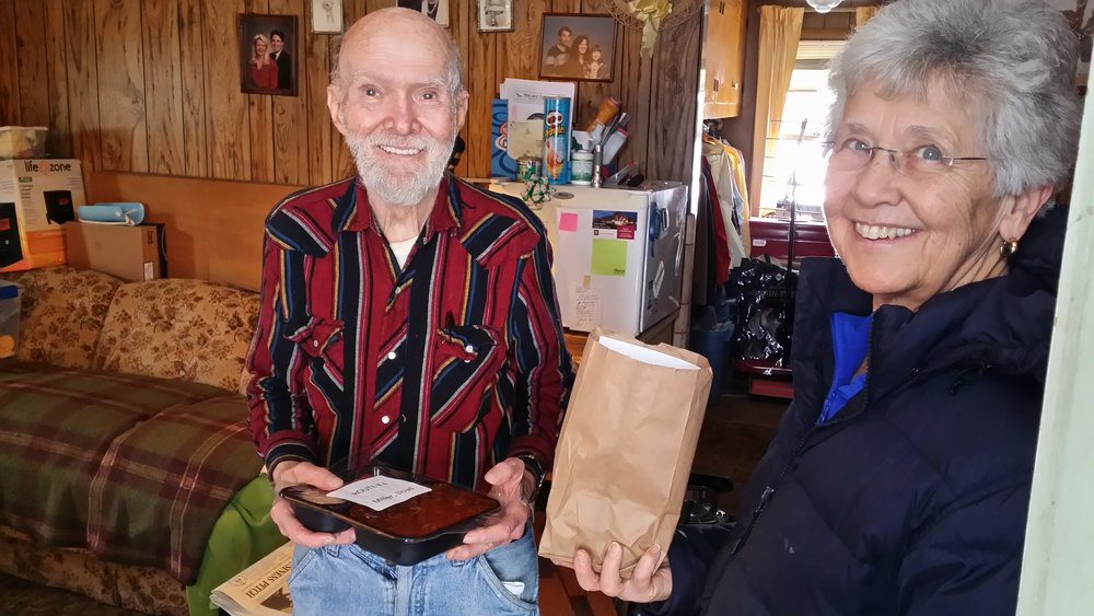 A Meals on Wheels of Goshen volunteer delivers a hot noontime meal.