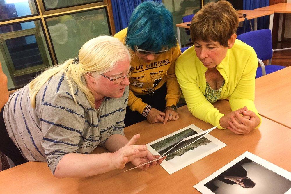 Una voluntaria y dos participantes comentan una foto durante la realización del Proyecto Cámara Lúcida; un curso de fotografía para personas ciegas en Las Palmas de Gran Canaria.