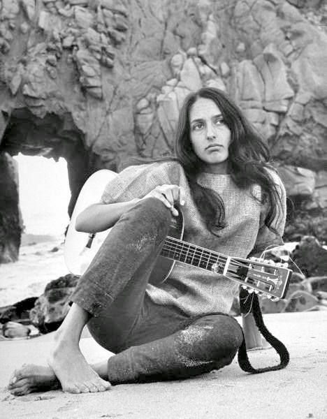Pretty and pensive Joan Baez on the beach.
