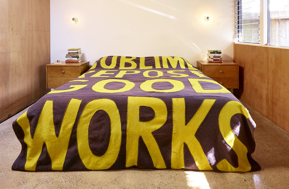 "Sublime Repose Good Works (Blanket) 2012  Reverse appliqué. Dyed yellow and purple upholstery-weight wool. Sewing. Sublime Repose / Good Works originally came from a  drawing  I made in 2008. Mel saw a version as a ""billboard"" painting in 2010. (The full text was: REFORM / DECENCY / SUBLIME / REPOSE / GOOD WORKS ). Photo: Jeffrey Cross"