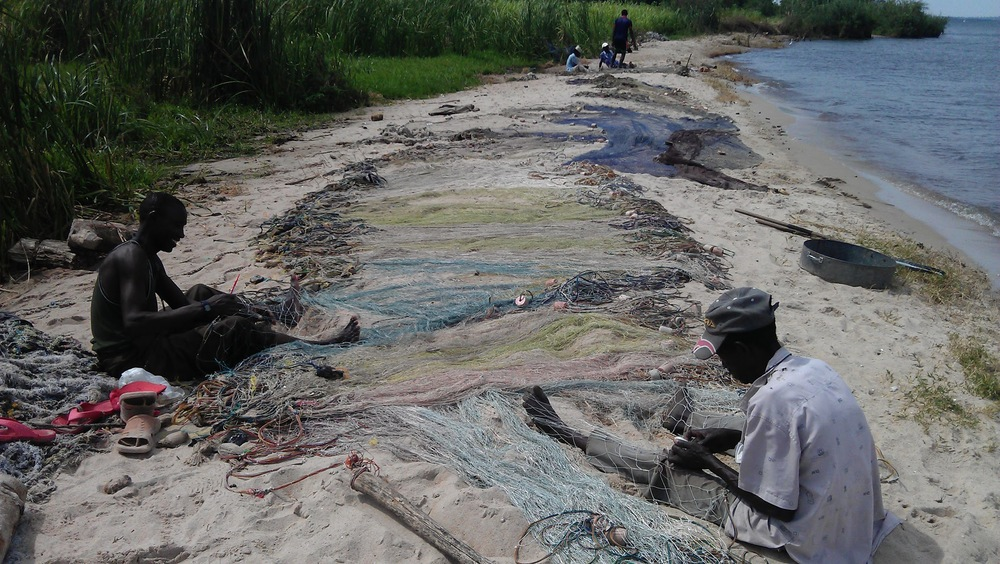 Fishermen repairing nets on the banks of Lake Vic