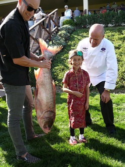 A young guest is all smiles when Chef Ryan Morgan, Executive Chef of Theory at OMSI, holds up the Asian carp, which is almost as tall as her, with Chef Parola enjoying the moment.