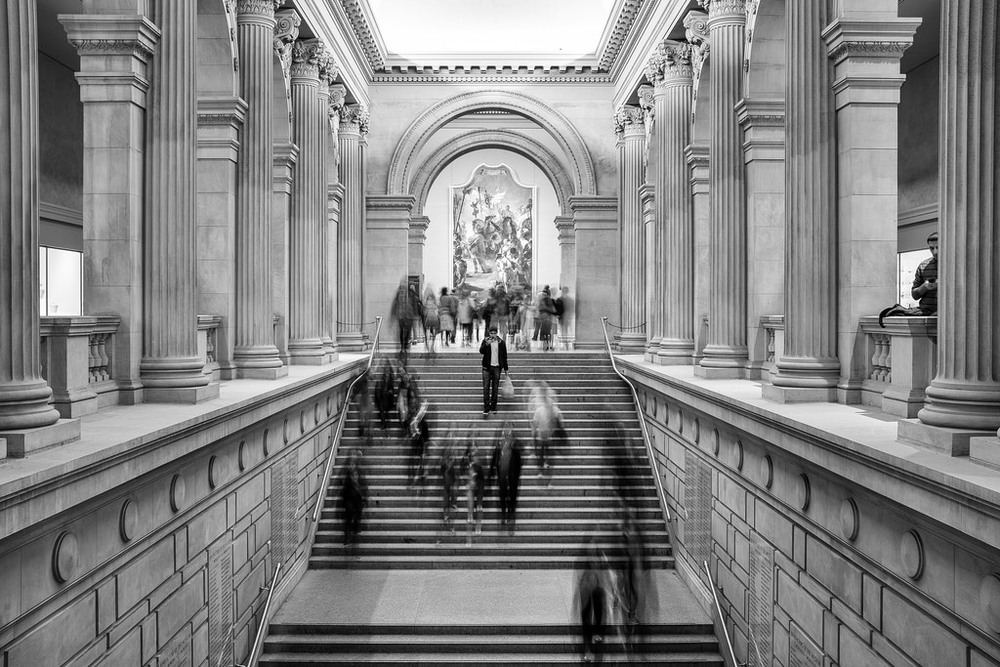 """Man in the Middle"" January 2014, New York City   Fujifilm X100s, 23mm, f/8, 2.1 sec, ISO 250   On a rainy weekend in January, my wife and I went to New York's Metropolitan Museum of Art. I was playing around with a slow shutter speed to give this stoic scene of the Grand Staircase a sense of energy. But then this guy stopped right in the center to check his phone, which froze him while everyone else blurred. Totally unplanned. But it totally made the shot. This may be the only instance in history where a guy checking his smartphone has actually improved a photo."