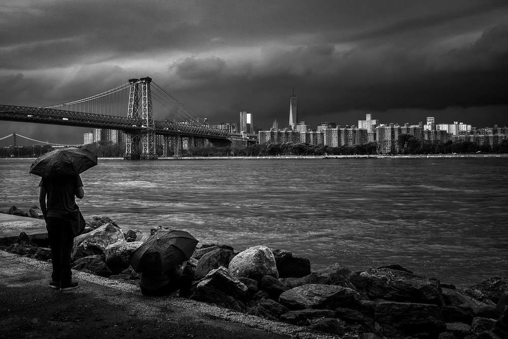 """Watching the storm roll in"" June 2014, Brooklyn, New York  Fujifilm X100s, 23mm, f/8, 1/150, ISO 320   This photo was taken just eight minutes earlier than the one above. I started shooting this scene down low along the rocks. But then I stood up and saw the couple with the umbrellas. As a rule of thumb, people are almost always more interesting than rocks."