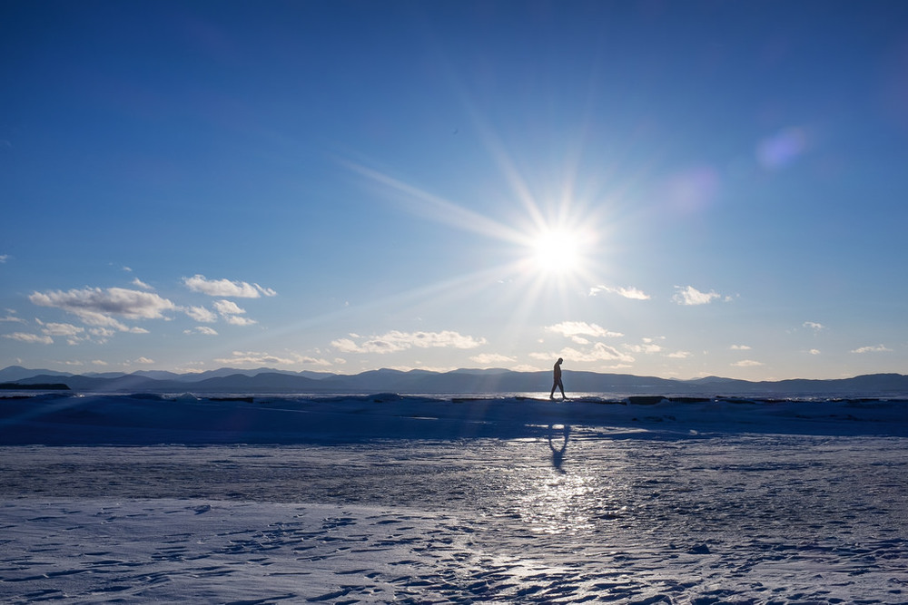 """The Long Walk Back"" March 2014, Burlington, Vermont Fujifilm X100s, 23mm, f/16, 1/320, ISO 200   When we checked into our hotel in Burlington, the concierge suggested we take a walk across the frozen Lake Champlain. This seemed like a terrible and dangerous idea. But sure enough, people were out there traipsing around all over the ice. So we took a walk on the lake. After all, ""when in Rome."" Sure enough, it was frozen solid, clear across to New York. This is the first time the winter has been cold enough for the lake to freeze since 2007."