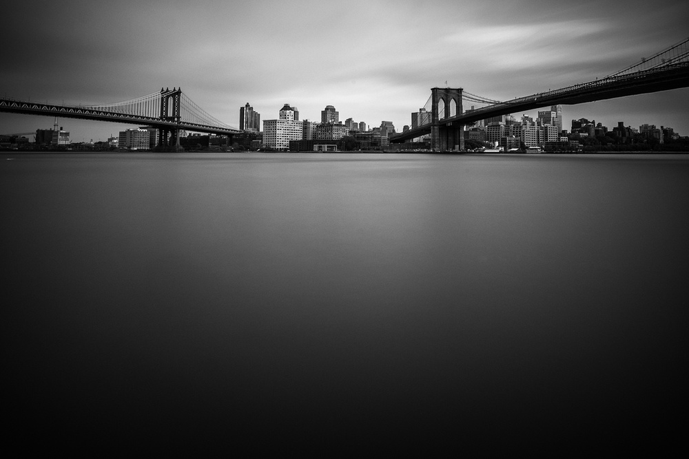 """Two Bridges"" May 2014, New York City Fujifilm XPro1, 14mm, f/8, 250 seconds, ISO 200   Sticking with the bridge theme, here's one of the Manhattan and Brooklyn Bridges that I shot from the East River Promenade. This was a four minute long exposure, which made the water on the East River go silky and created the sense of movement in the clouds."