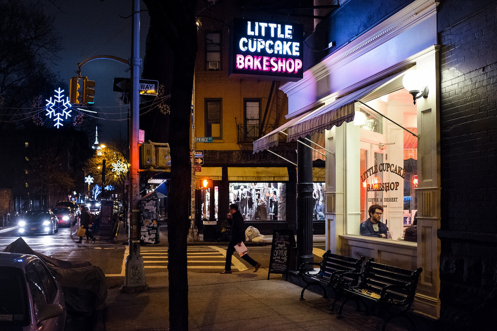 """Little Cupcake Bakeshop"" January, 2014 New York City Fujifilm X100s, 23mm, f/2.8, 1/105 seconds, ISO 6400   I love the feeling of this photo. There's something kind of  Edward Hopper  about it. And there are so many little details. The glimpse of the Empire State Building in the distance. The snowflake decorations that make the cupcake shop feel just a bit cozier. And the fact that the two people crossing on either corner of the street are perfect mirror images of each other."