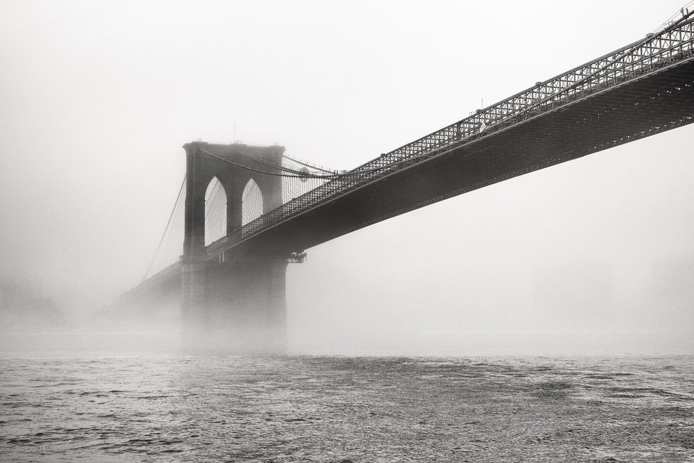 """Brooklyn Bridge Fog"" April 4, 2018. East River, New York City Fujifilm XPro2, 35mm, f/4, 1/1500, ISO 200   There's usually a whole city skyline in this shot. But on this morning, the fog was so thick, it created a white seamless backdrop behind the Brooklyn Bridge."