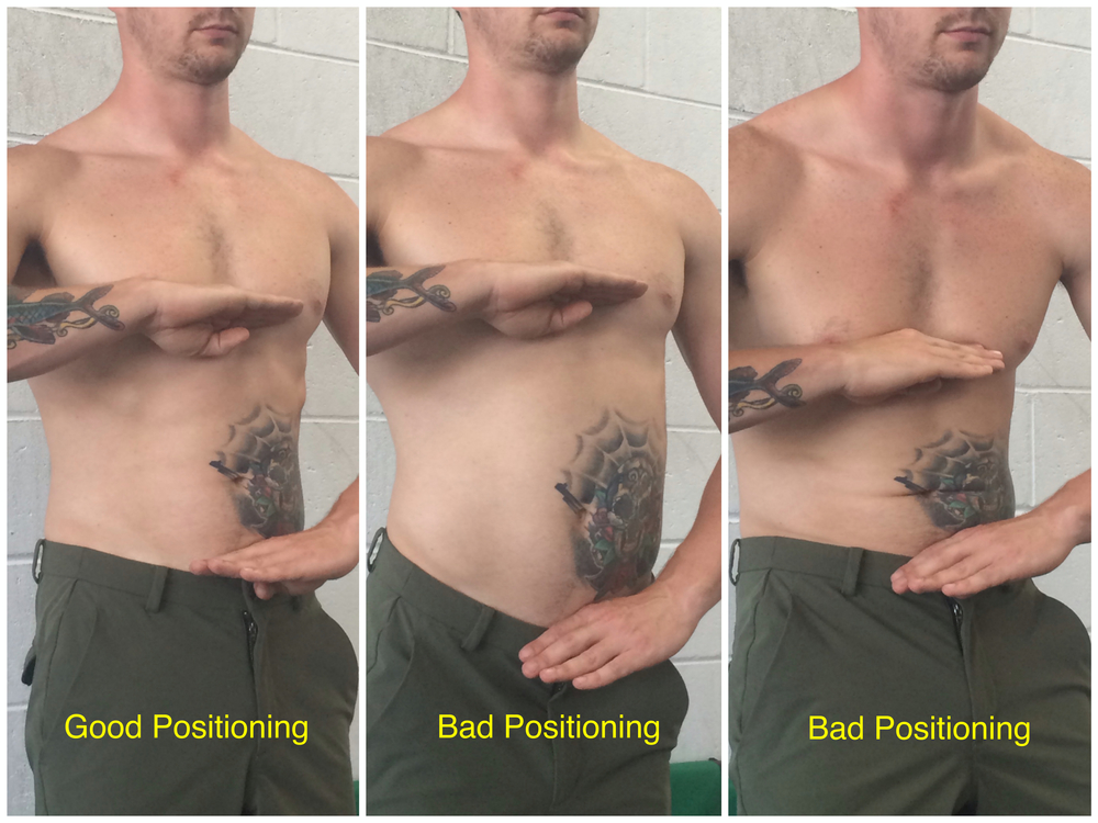 This nice, tattooed man demonstrates the Two-Hand Rule of pelvic neutrality.
