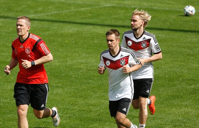 Photo: Ina Fassbender/Reuters. German national soccer team fitness coach Darcy Norman (left) and players Marcel Schmelzer and captain Philipp Lahm run during a training session.