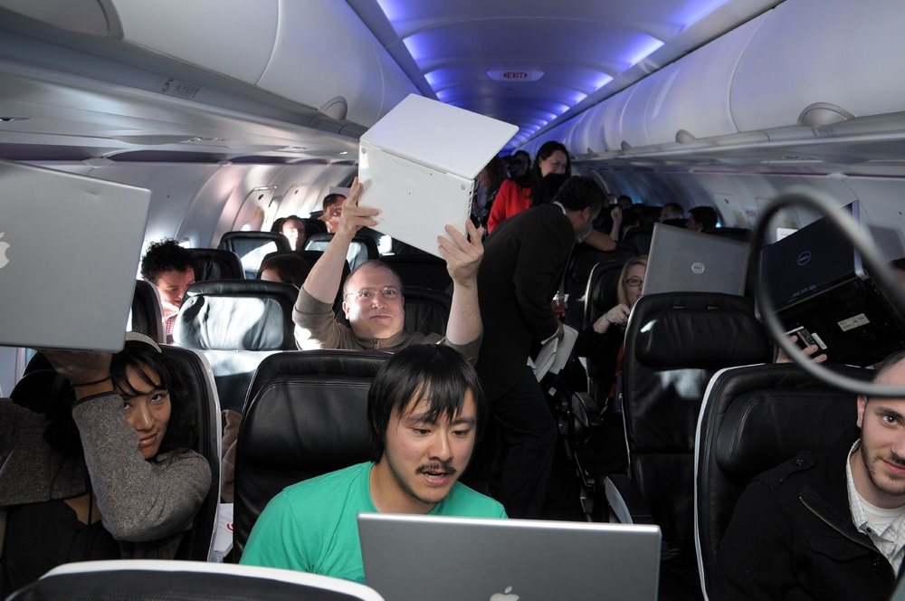 Me holding up a laptop on the inaugural Wi-Fi flight of Gogo service on Virgin America. That's Brian Lam and Ryan Block in the row ahead of me.
