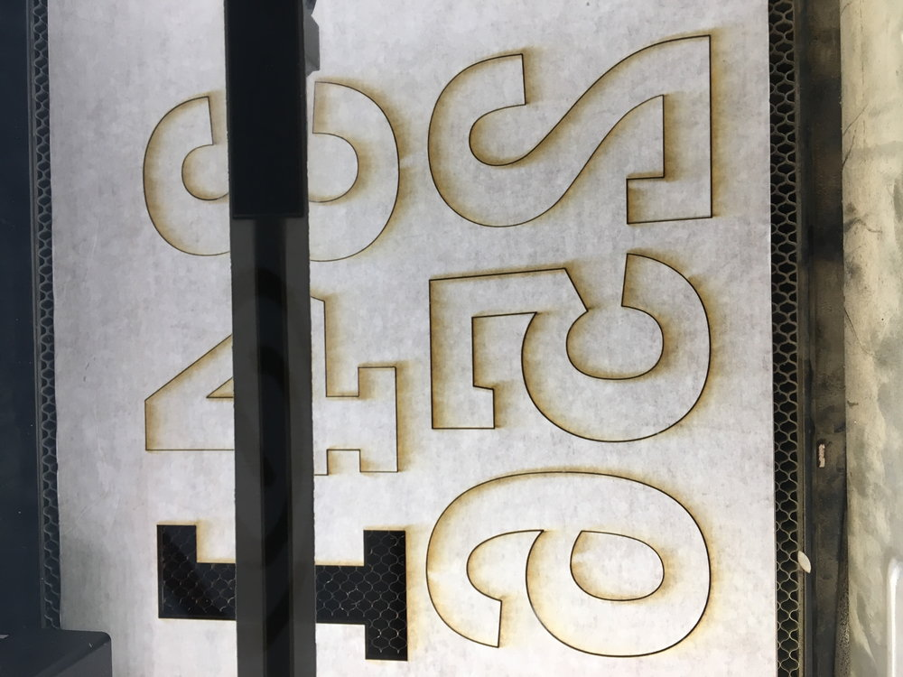 Letters being cut on a Glowforge.