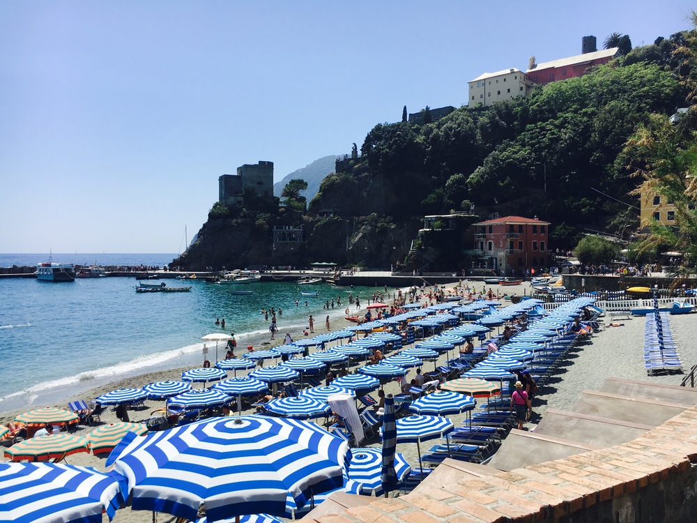 striped umbrellas on the beach of Monterosso al Mare, Cinque Terre, Italy