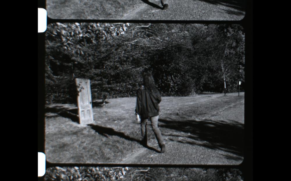 16mm film still from Cemetery Writer: The Door by Geena Matuson (@geenamatuson).
