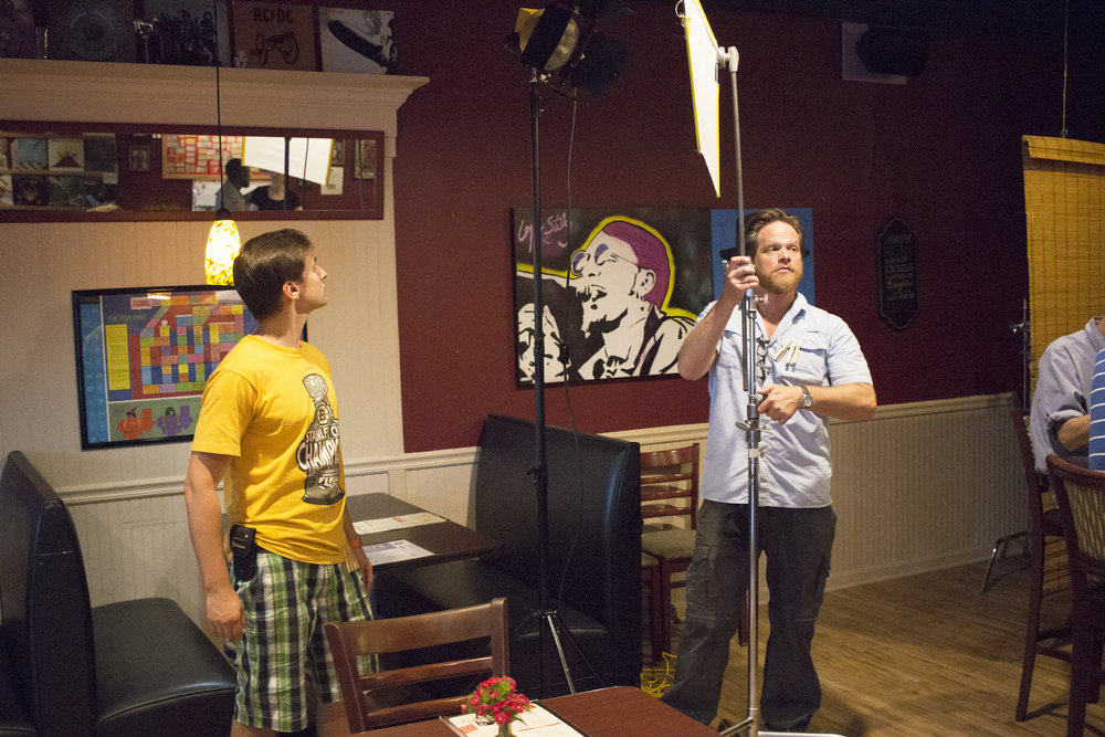 Assistant Grip Andrew Frechette with Grip/Gaffer Dan Perez de la Garza on the set of Geena Matuson's production of 'Fauxmercials' bar ads, September 2016.