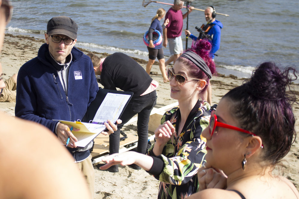 Writer, Producer/Director Geena Matuson gives direction to Actors as Assistant Director Adrian Atwood takes notes on the set of Geena Matuson's production of 'Fauxmercials' beach ads, September 2016.