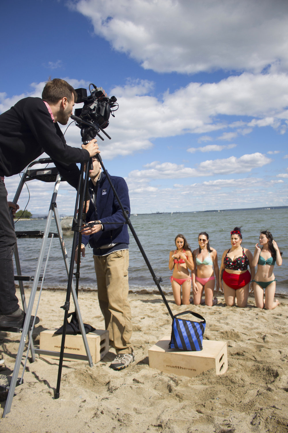 Director of Photography Denez McAdoo sets up the shot, with Assistant Director Adrian Atwood and Actors Acei Martin, Catalina Snape, Alessandra Grima and Maya Simone on the set of Geena Matuson's production of 'Fauxmercials' beach ads, September 2016.