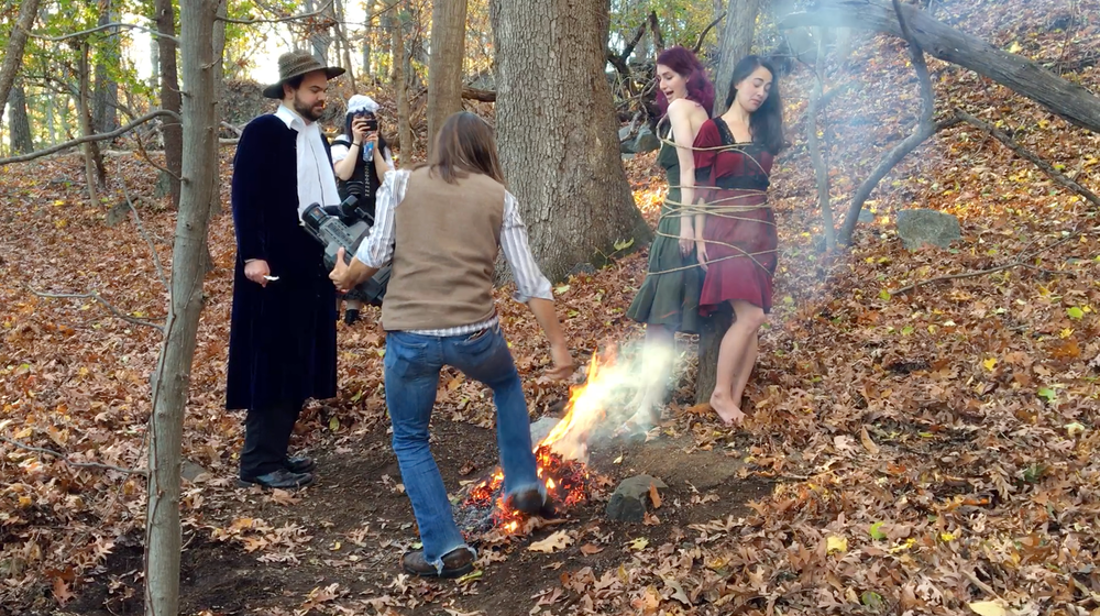 John Hartman of  Reel Groovy Films  on camera captures witches  Geena Matuson  (@geenamatuson) and  Maya Simone  burning at the stake. At back,  Eve Xastur  takes some photos while pilgrims Dawn Nightshade bears witness, 2016.