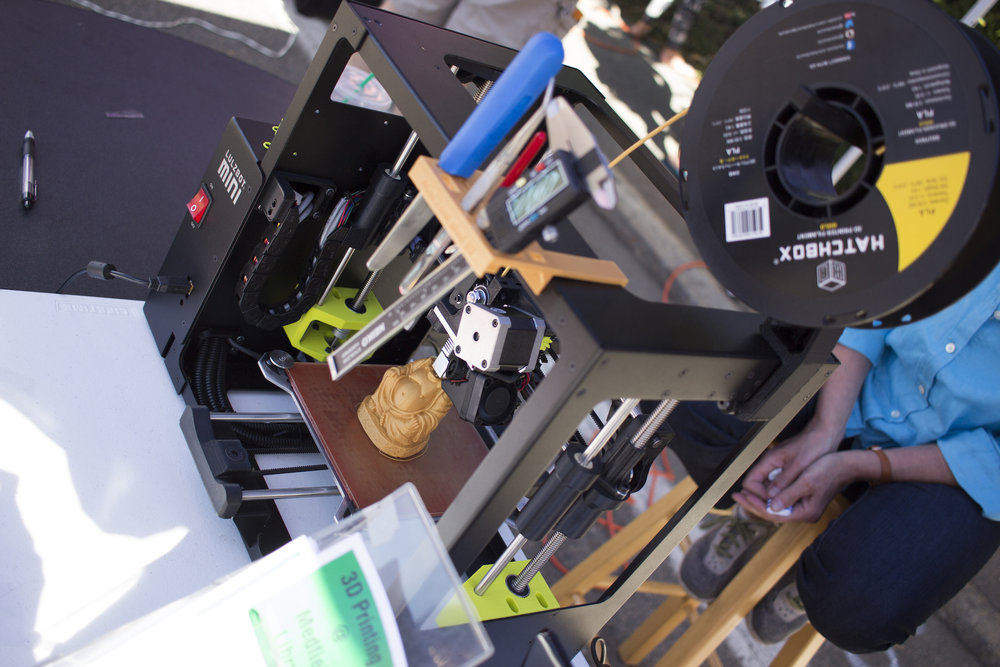 The library's 3D printer in action, working on a Buddha figurine.