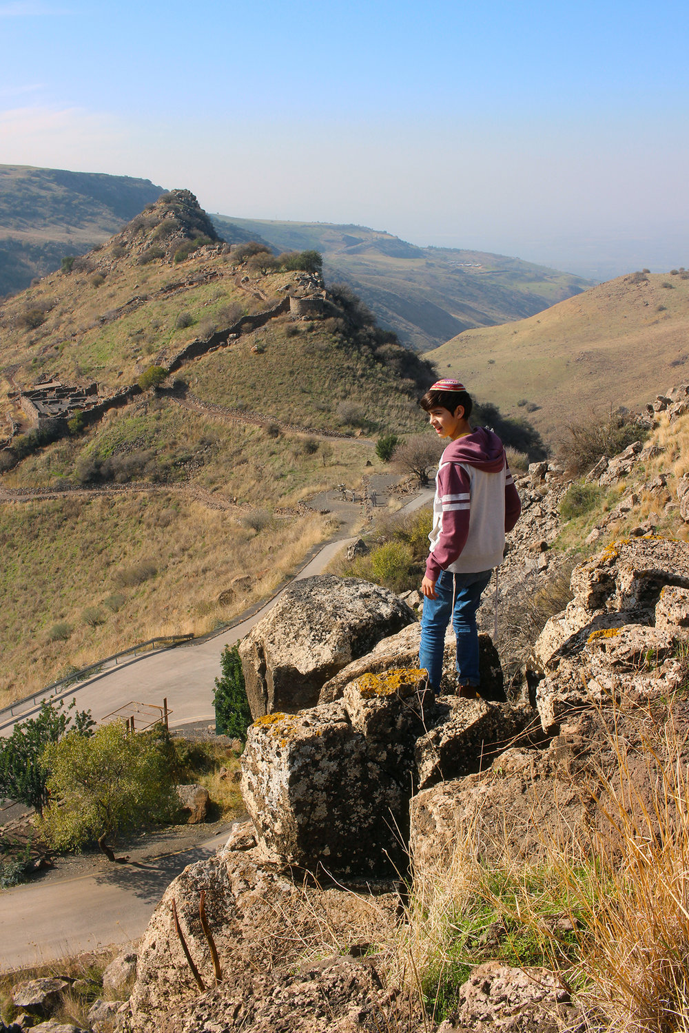 A boy stands atop a steep mountain of Gamla in Golan Heights, Israel.
