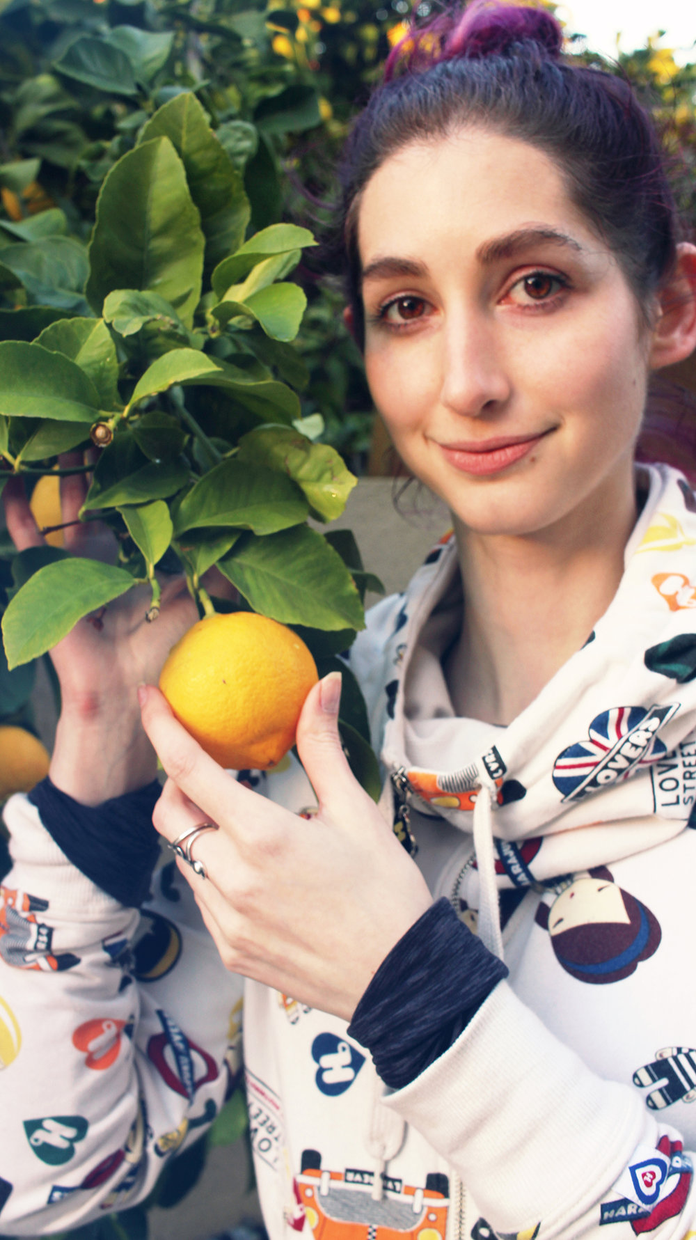 Geena fondles an orange in the backyard of Nir's family home in Hadera, celebrating the second night of Hanukkah with Shorashim Israel, 2016.