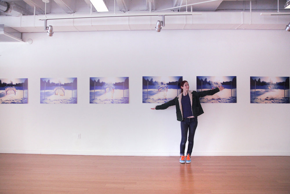 Geena Matuson (@geenamatuson) stands before her art print series at her TransFIREmation Gallery Show & Installation in the MassArt Student Life Gallery in Boston, MA, US.
