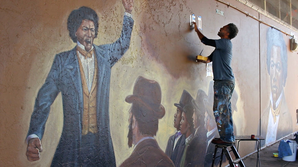 Children's book illustrator London Ladd paints murals of Frederick Douglass and Martin Luther King Jr. in Syracuse, NY, 2018.