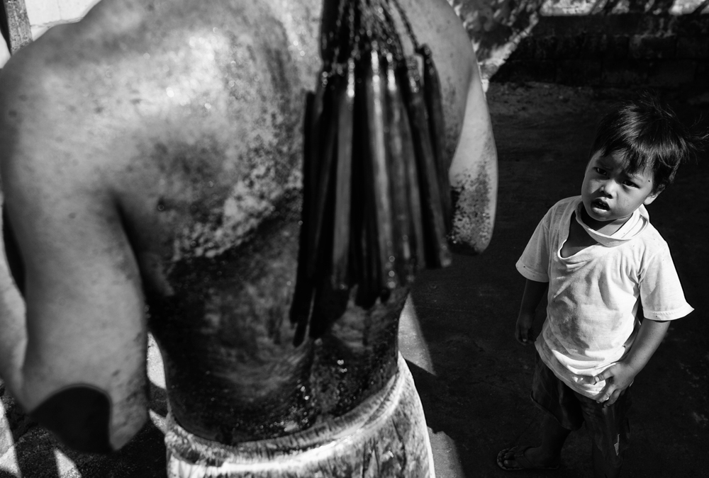 A boy looks at his father's wounds after his father made him whip his back as a ritual to mark the death of Jesus Christ on Good Friday in Cutud town in Pampanga province, north of Manila