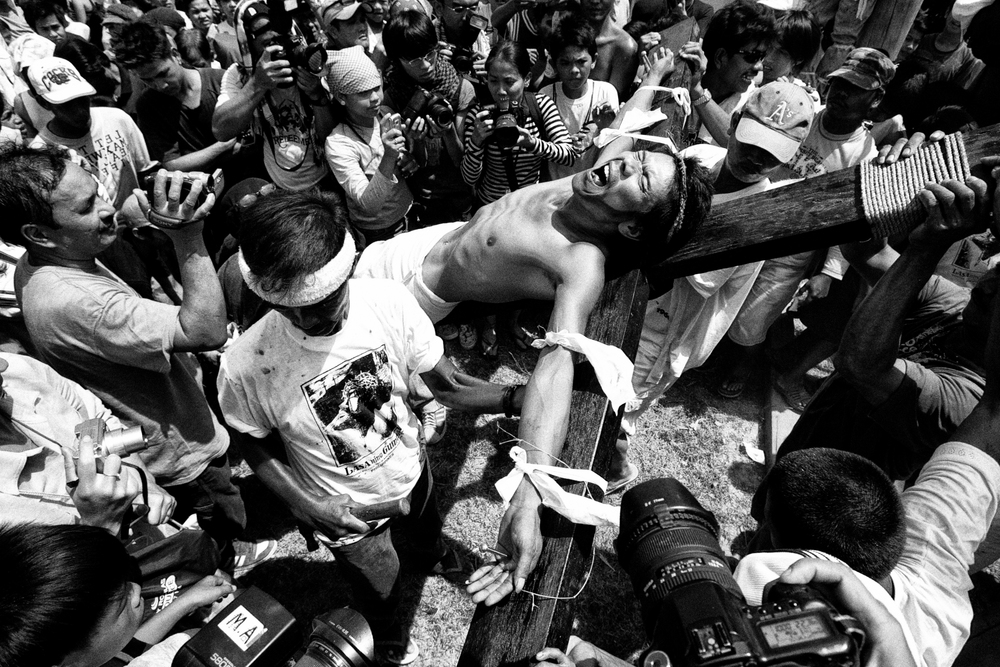 A penitent cries he is brought up to be presented to the audience after being nailed on a wooden cross in a voluntary ritual to mark the death of Jesus Christ on Good Friday in Cutud town in Pampanga province, north of Manila
