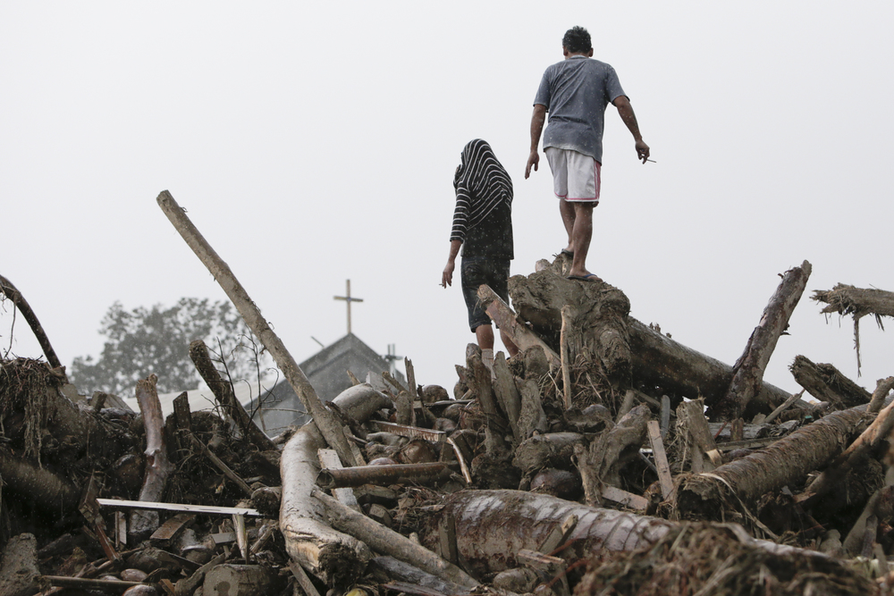 Men climb up washed up logs as they look for bodies to be recovered in New Bataan, Compostella Valley on December 7, 2012.