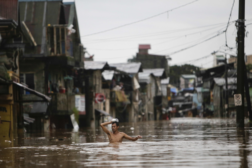 A man wades through floodwaters in Tumana, Rizal Province August 20, 2013. Monsoon rains reinforced by a tropical storm flooded half the Philippine capital in just 24 hours, triggering landslides and killing at least seven people, officials said on Tuesday. REUTERS/John Javellana (PHILIPPINES)