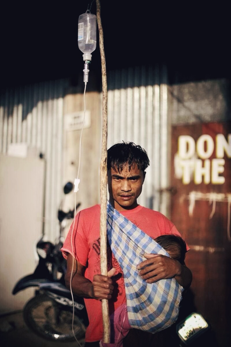 A father holds an improvised dextrose stand as he carries his child at a hospital in Mayoyao, Ifugao Province north of Manila, Philippines.