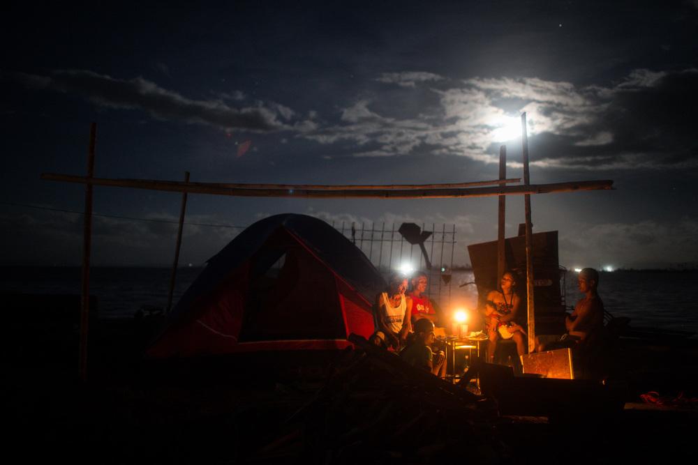 Typhoon Yolanda survivors waiting for dinner under the full moon in Tacloban November 19, 2013.