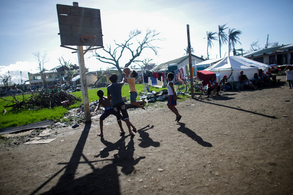 Children displaced by Typhoon Yolanda play basketball inside an evacuation center in San Jose, Tacloban November 25, 2013.