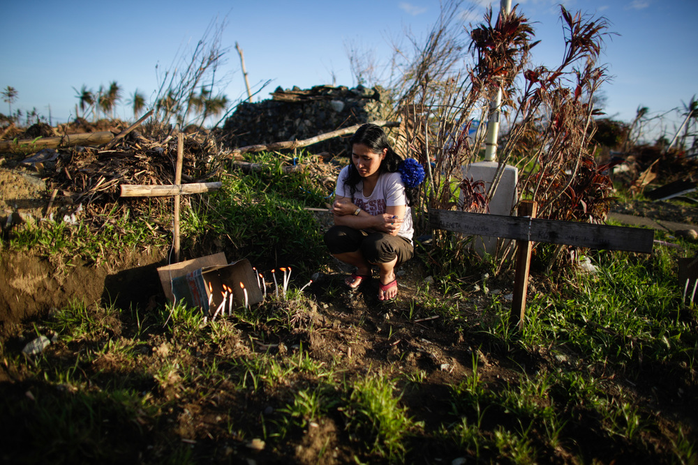 A woman grieves for a loved one at a mass grave in Tanauan, Leyte.
