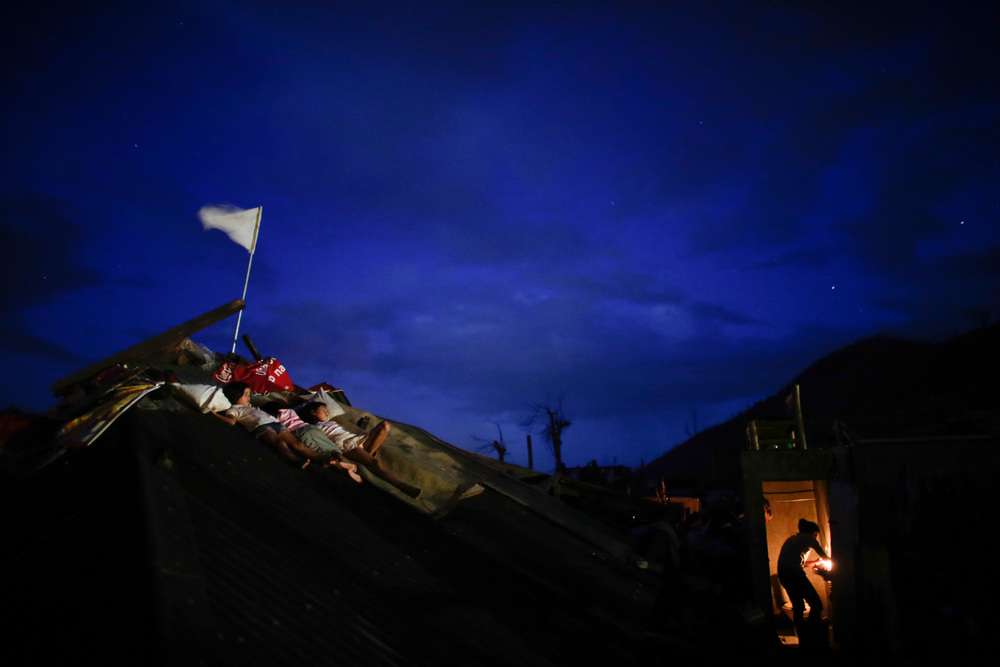 Children sleep on the collapsed roof of their house as their mother prepares dinner in Palo, Leyte