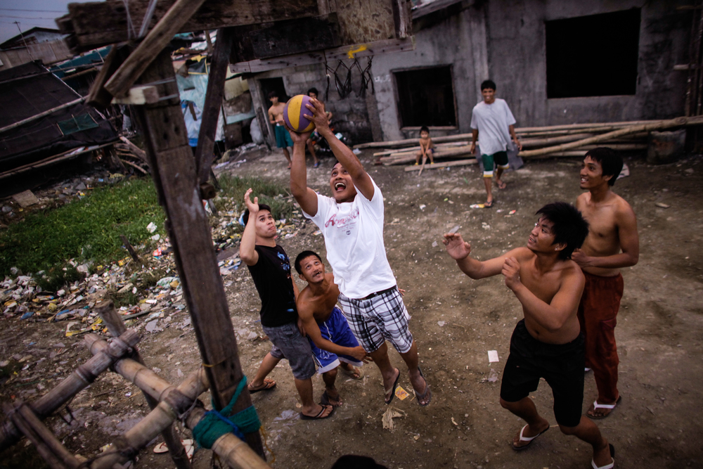 Survivors of Typhoon Parma play basketball at a court they had just repaired in Malabon