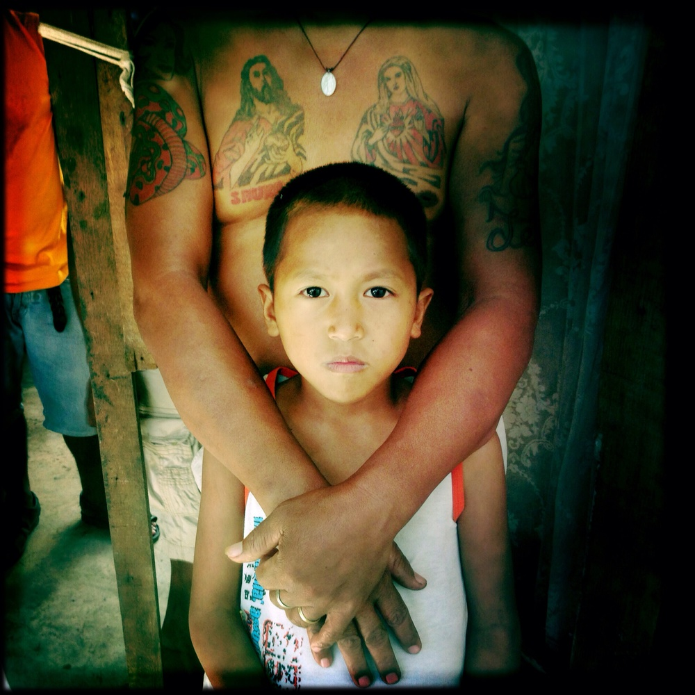 A child of an inmate who fled and voluntarily returned to jail poses for a portrait inside a prison in Leyte. A number of the inmate's families have been living inside the jail as they have been made homeless by typhoon Yolanda.