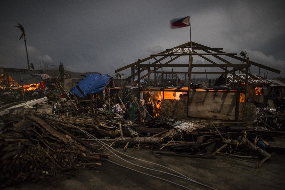 A survivor is seen inside his home that was damaged by typhoon Haiyan in Marabut, Samar.