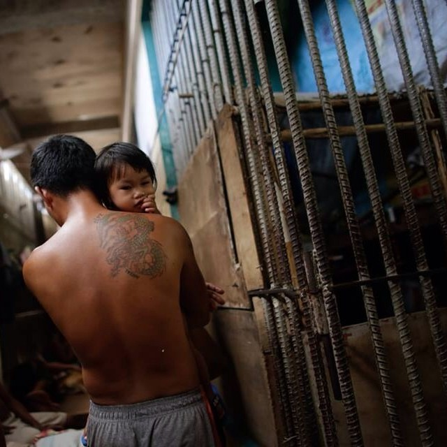 An inmate carries his child who has been living with him inside the Leyte Provincial Jail as they were made homeless by Typhoon Haiyan. Last Thursday, nearly 200 of the inmates staged a jail break, complaining of a lack of food and the uncertainty of thei
