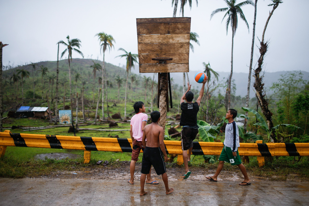 Survivors of typhoon Pablo play at a makeshift basketball court in a highway in Lingig, Surigao del Sur Mindanao Province Philippines
