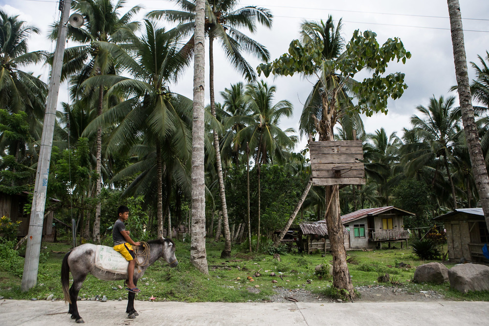 A boy riding a horse is seen in front of a makeshift basketball court in the province of Iligan, Mindanao Region south of the Philippines